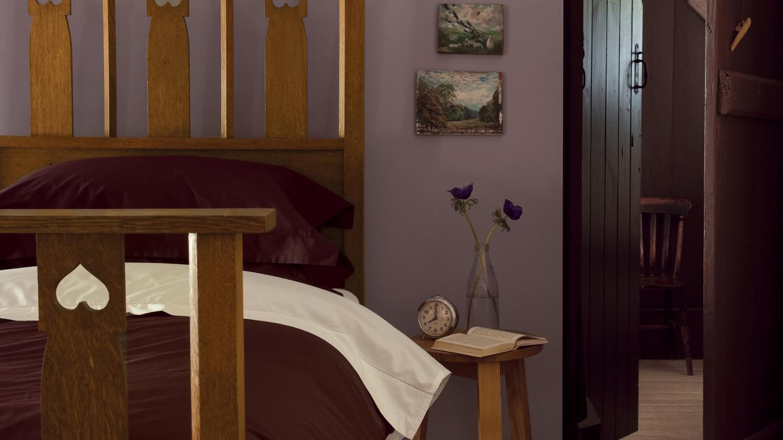 Purple walls bring warmth and nostalgia to this comfortable bedroom.