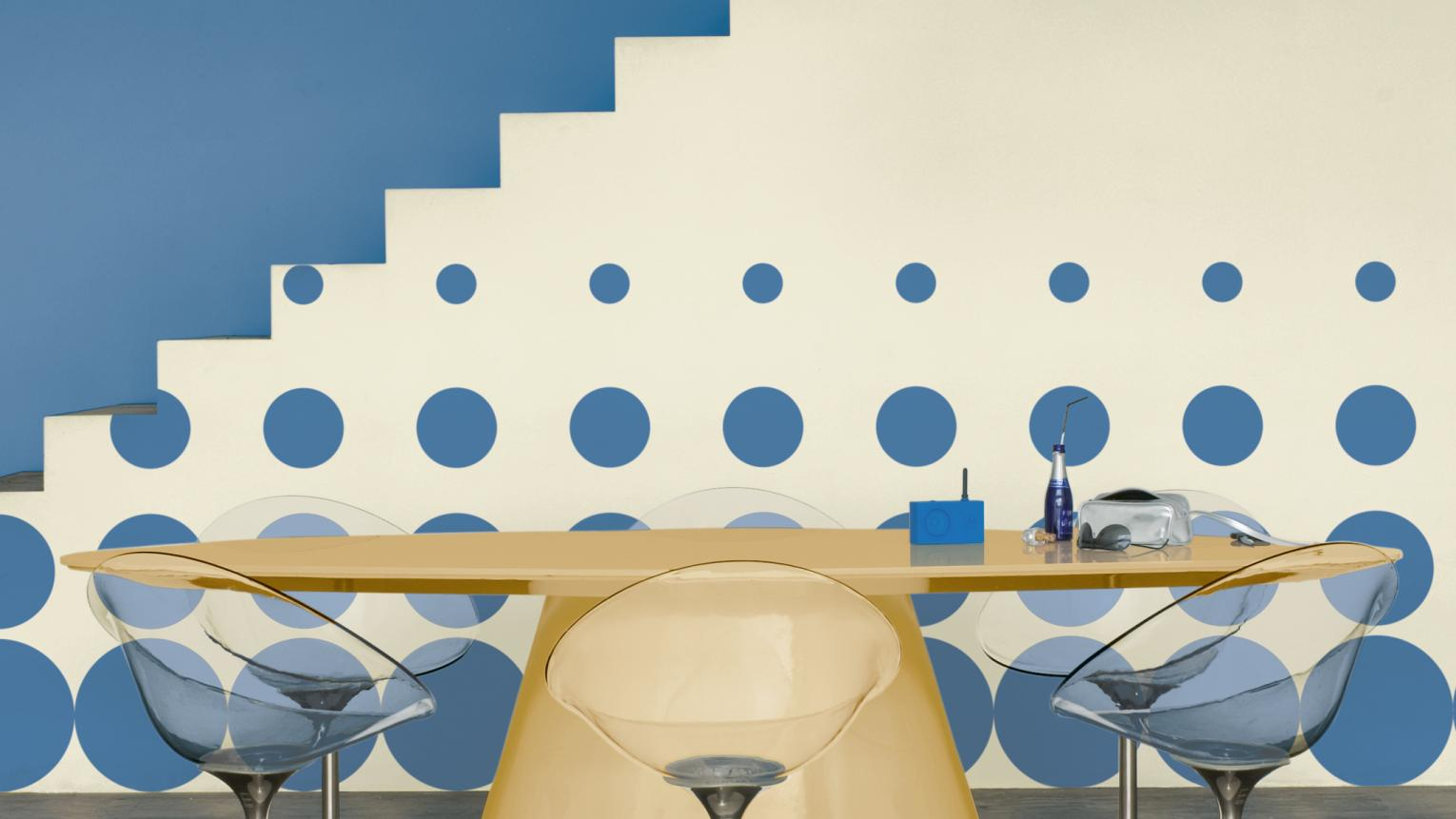 Bold blue walls, ceiling and circle motifs add depth to cream.